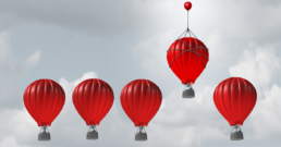 Game Changer and business advantage concept as a group of hot air balloons racing to the top but an individual leader with a small balloon attached giving the winning competitor an extra boost.