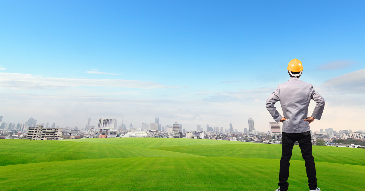 Field Service Engineer standing, on green grass field with Building background